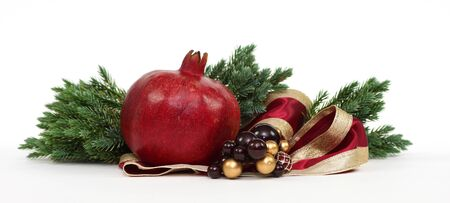 Christmas Pomegranate arrangement with pine boughs and red ribbon photo