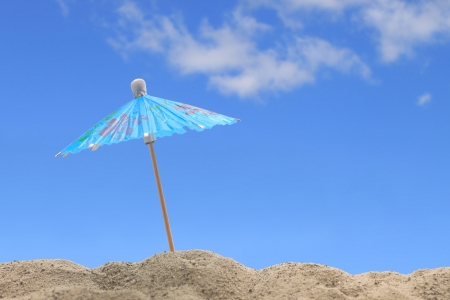 A cocktail umbrella sits atop a sand dune on a lovely summer day