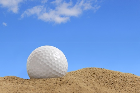 Shiny new golf ball in the sand on a sunny day Stock Photo - 17471966