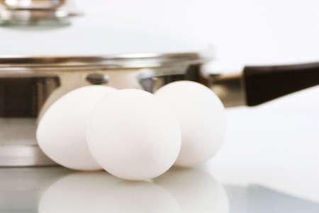 흰색에 작은 스테인리스 냄비와 세 흰색 닭고기 달걀