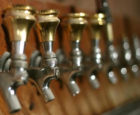 挨りだらけの古いビールの行が放棄されたバーにタップします。 写真素材