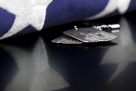 Dog tags or ID tags, once worn by a military verteran with a folded US flag