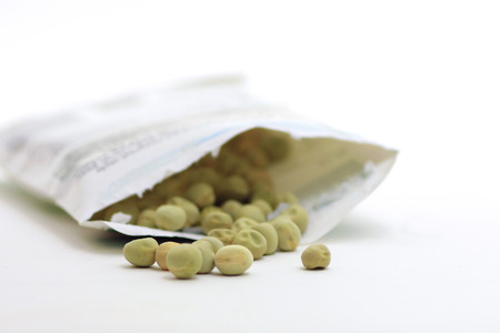 Packet of pea seeds on white