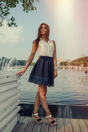 Young attractive brunette dressed skirt and blouse in Moscow summer park
