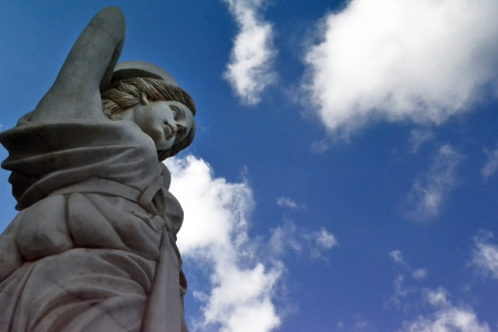 forlorn: statue of a girl against the sky
