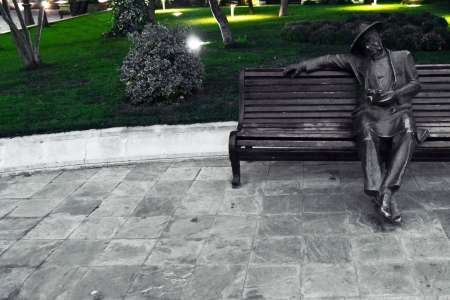 statue of a man on a bench in the park Stock Photo