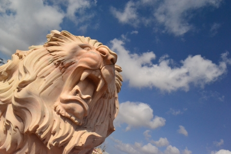 a statue of a lion on a background of the sky