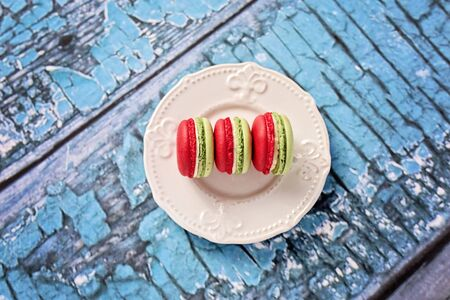 Sweet and colorful french macaron on blue wooden background.