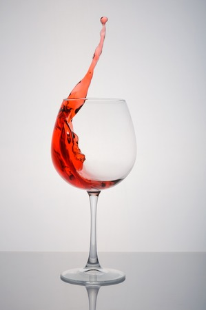 glass of red wine splashing on a white background Stock Photo
