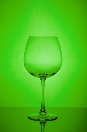 The empty wine glass on green background