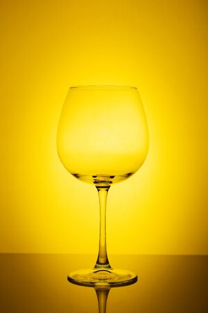 Empty wine glass on yellow background