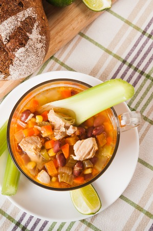 Mexican soup with chicken, celery and vegetables on tablecloth Stock Photo