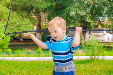 A boy plays with a volleyball net in the Park Stock Photo