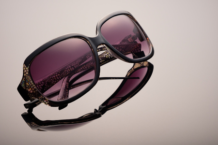 Sunglasses using soft focus on a black glass surface, with a gradient of light, reflexes and reflections, copy space