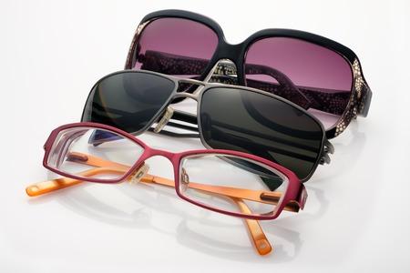 Three sunglasses and optical glasses on white background Stock Photo