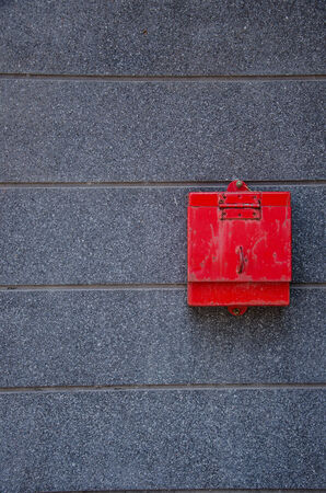 red mail box put on gray flagstone photo