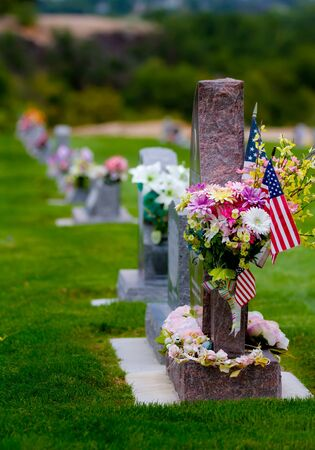 Flowers and flags on a headstone with a row of headstones in the background Stock Photo