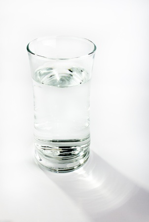 A single glass of water against a light gray background. Shadow commnig off the glass is visible
