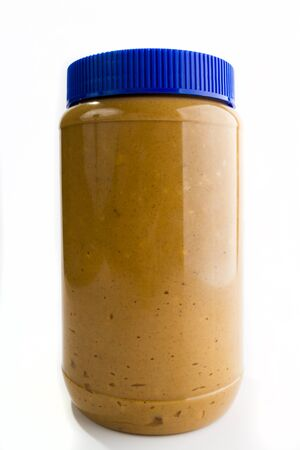 Single tall jar of peanut butter with a highlight reflection on the right side. image is against a light background