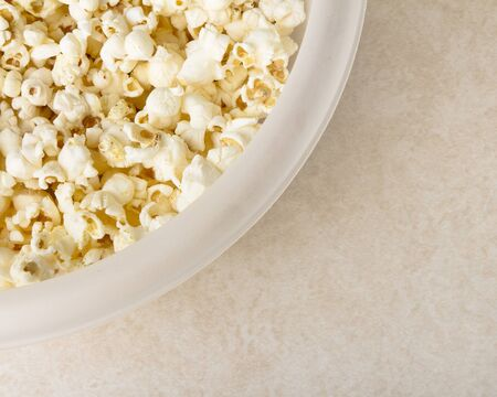 Bowl of buttered popcorn covering large portion of frame with copyspace in lower left