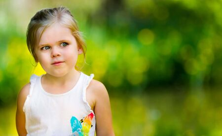 Young girl is against a green background with yellow highlights. lots of open copy space and girl is looking into the blank area. Image has a very shallow depth of field with focus only on the girl
