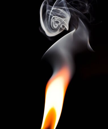 Flame isolated against a black background with smoke swirling above