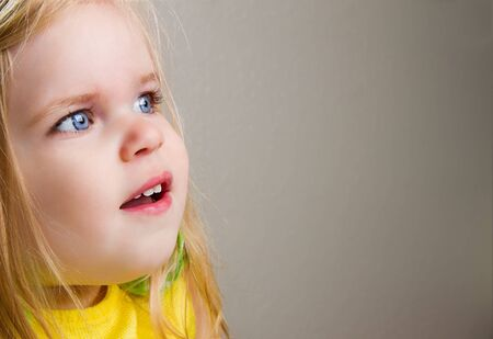 Young child is smiling while facing to the right with her big bright blue eyes. Lots of copyspace.