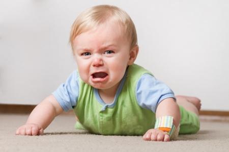Un bebé joven que tiene un ajuste en el suelo llorando y haciendo una mueca mohín
