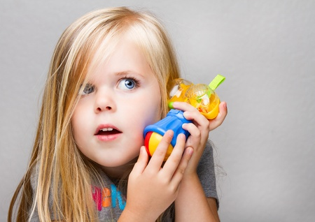 make believe: Young girl trying to use a toy hammer as a phone or just having fun playing make believe Stock Photo
