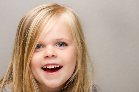 A Close up shot of a young girl laughing isolated against a medium gray background. Stock Photo