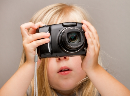 studio picture: Young child holding a point and shoot camera. Focus is on the camera as she is about to push the button