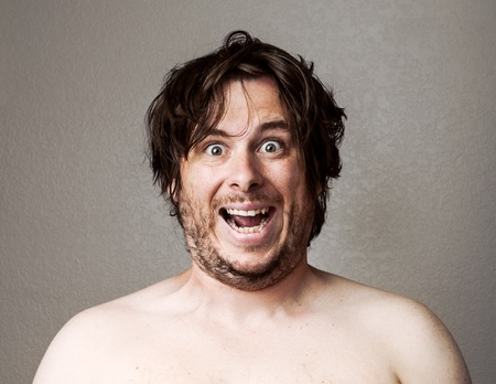 Topless man making a creepy looking smile at the camera against a lightly textured background