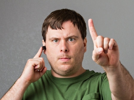 interrupt: Man on a headset getting getting firm with putting a finger up to show that he is on a headset and not wanting to be interupted.