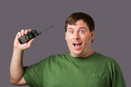 Man holding up his retro old school cell phone and is very happy. This thing is from the late 90s early 2000s. Even has the pull out antenna Stock Photo