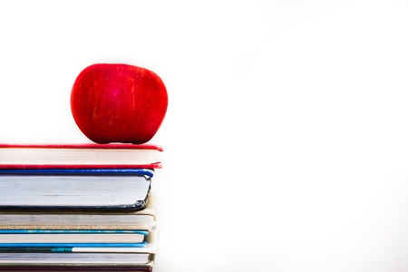 Stack of books with a single red apple on top Stock Photo