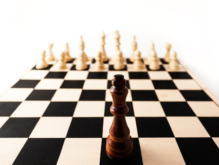 Black chess piece with a stretched perspective alone up against many white pieces. can stand for racism, challenge, adversity, diversity, courage,  or many other challenges in life.