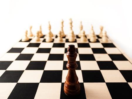 racismo: Pieza de ajedrez negro con una perspectiva estirada solo en contra de muchas piezas blancas. puede representar el racismo, el desafío, la adversidad, la diversidad, el valor, o muchos otros desafíos de la vida. Foto de archivo