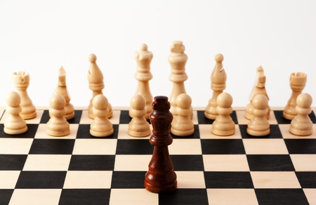 Image of a single black piece standing in front of bunch of white pieces, Can be used for racism, diversity, challenge, courage, adversity, or many other uses.