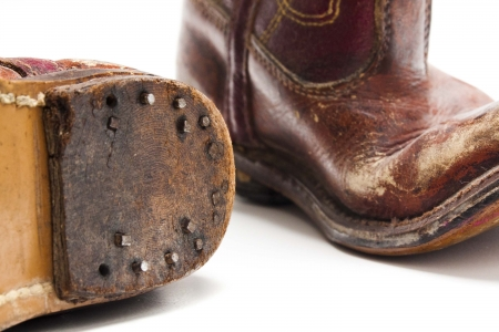 Old worn out pare of cowboy boots from someones childhood days against a white background