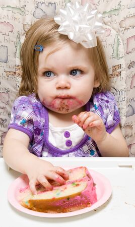 Girl eating a slice of cake and making a mess