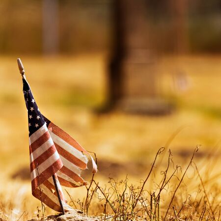 Worn out american flag against a dried out field background