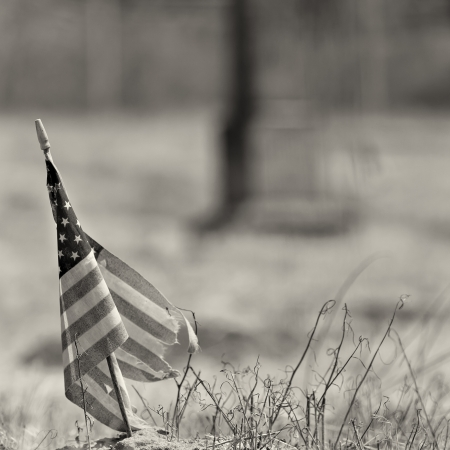 Tattered american flag taken at and old cemetary with monument in background  shallow field of fiew with focus on flag