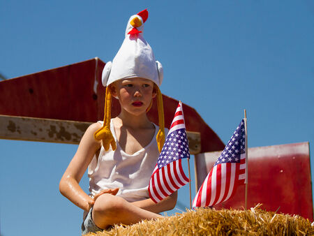 MIDDLETON, IDAHO - JULY 4: Unidentified child sitting on some hay with some american flags during the 4th of july parade 2012 in Middleton, Idaho Editorial