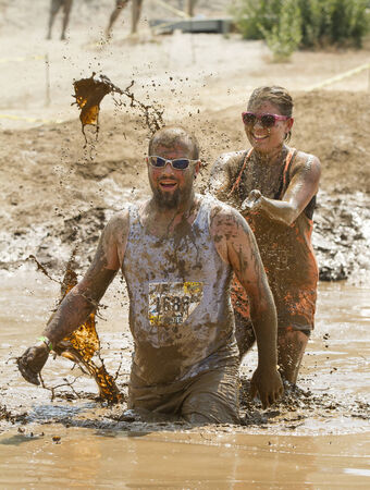 mud pit: BOISEIDAHO AUGUST 25: Runners in The Dirty Dash playing in the mud. One runner is splashing her friend. This took took place in Boise, Idaho on August 25, 2012 Editorial