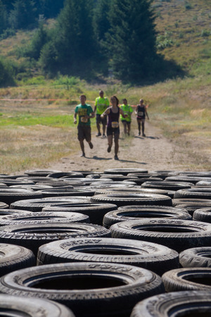 BOISE, IDAHOUSA - AUGUST 10: Group of runners race to the tire course at the The Dirty Dash in Boise, Idaho on August 10, 2013. Focus is shallow and set on the tires