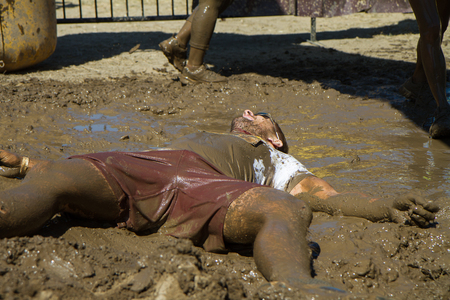 BOISE, IDAHO/USA - AUGUST 10: Unidentified man just lays in the mud at the The Dirty Dash in Boise, Idaho on August 10, 2013