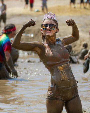BOISE, IDAHOUSA - AUGUST 11: Unidentified runner coverd in mud wearing a crown poses strongly at the The Dirty Dash in Boise, Idaho on August 11, 2013