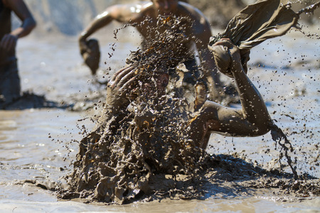 BOISE, IDAHO/USA - AUGUST 10: Unidentified person makes a huge splash in the mud. Event was held at the The Dirty Dash in Boise, Idaho on August 10, 2013