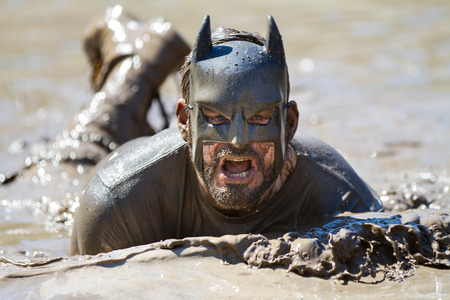 BOISE, IDAHOUSA - AUGUST 10: Runner dressed as batman swims in the mud during the The Dirty Dash in Boise, Idaho on August 10, 2013