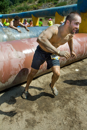 BOISE, IDAHOUSA - AUGUST 11: Unidentified runner gets off to a run after finishing up on of th obstacles at the The Dirty Dash in Boise, Idaho on August 11, 2013  Editorial